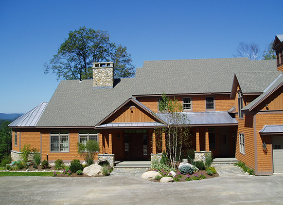 Picture of new wooden home with trees and shrub plantings in the front