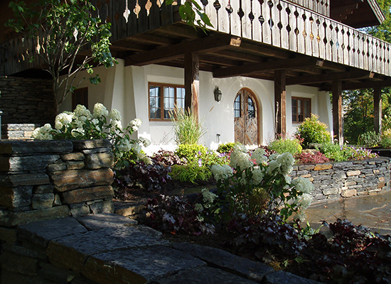 Picture of chalet style home with large flowering bushes and gardens
