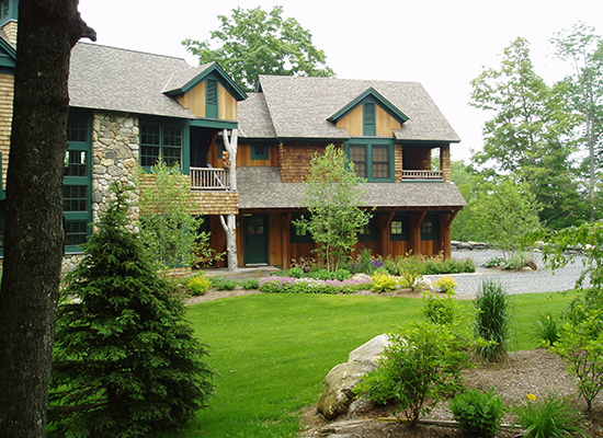 Picture of large shingle home with large trees and green plantings