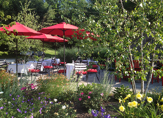 Picture of flower gardens for a resturant patio with red umbrellas
